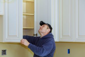 Man with blue hoodie and black hat installing white kitchen cabinets