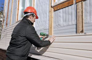 Man installing beige siding on a house