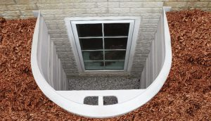 Exterior of basement window with white trim
