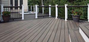 Dark brown wooden deck with white railing
