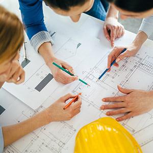 People huddled around a blueprint