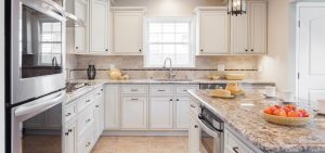Kitchen with marble countertops, white cabinets and steel appliances