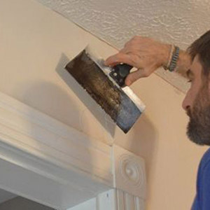 Photo of man repairing wall of home