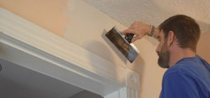 Man fixing wall in a home