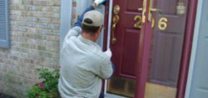 Man repairing exterior door of a house