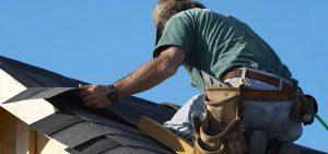 Man repairing shingles on roof