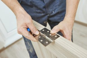 Man fixing hinge of door