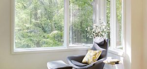 Gray chair by a large window overlooking trees